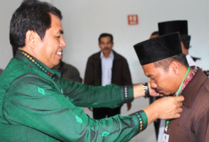 KABID Pendidikan Madrasah Kanwil Kemenag Sumut, Tohar Bayoangin, mengalungkan tanda peserta secara simbolis. (Adhif)